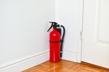 Fire Extinguisher Sitting Behind the Door at Home