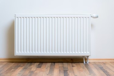 Home radiator heater on the white wall on wooden hardwood floor. Adjustable warming equipment for apartment and home