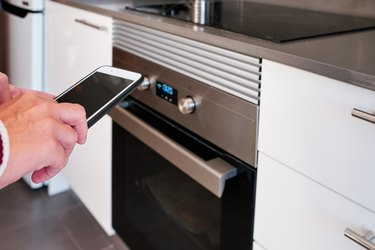 a woman using a smartphone to control the oven in the kitchen - intelligent home concept