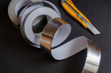 Aluminum insulation tape on a dark table.