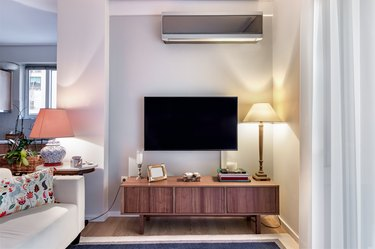 Wooden cabinet with flat tv and lamps on a small living room.