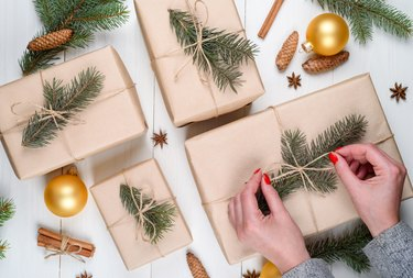 Christmas gift wrapping background, copy space. Female hands holding christmas present box wrapped in kraft, top view. Winter holidays concept, flat lay. Woman with red manicure packing Christmas gift