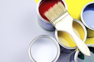 Multi-colored paint cans with a brush in a trendy color combination.