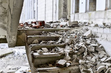 Stairwell concrete buildings littered with debris of stones and concrete