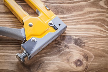 Staple gun on wooden board directly above construction concept