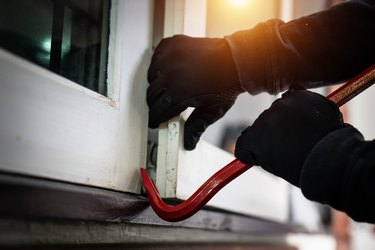 dangerous masked burglar with crowbar breaking into a victim's home door,concept