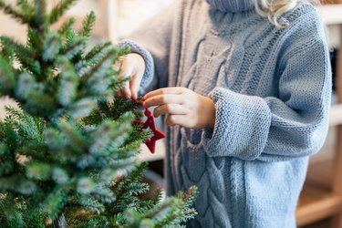 Little child girl is decorating Christmas tree with red ornaments. Kid is wearing in cotton knitted blue sweater.