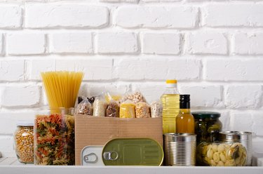 Set of uncooked foods on pantry shelf prepared for disaster emergency conditions on brick wall background