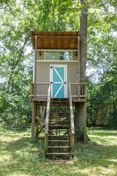 Large lush lot backyard of American house in the suburbs with a homemade tree house kid's children's playground