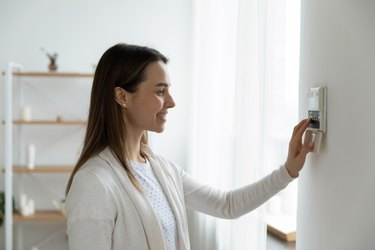 Smiling woman adjusting degrees set comfortable temperature using thermostat