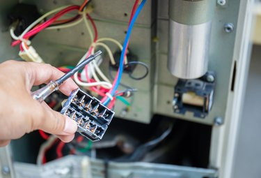 Close up of Air Conditioning Repair, repairman test, checking & repair of magnetic contactor and fixing air conditioning system