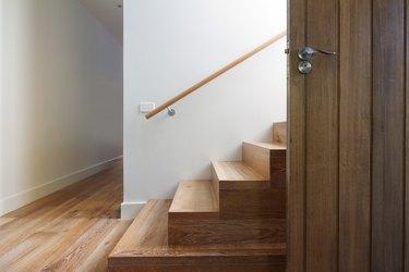 Modern staircase of oak wood beside front door horizontal