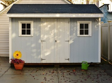 Blue and White Shed in Back Yard of House for Storage