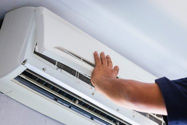 Air Conditioning Repair, Repairman fixing air conditioning system, Male technician service for repair and maintenance of air conditioners.