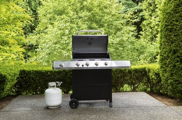 Large outdoor bbq cooker with white propane tank on home concrete patio