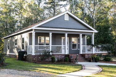 Close up of small blue gray mobile home with a front and side porch with white railing