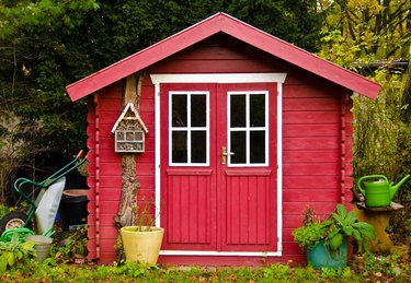 A light red small shed, gardenhouse, with some garden tools around it