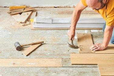 Carpenter laying new wood flooring