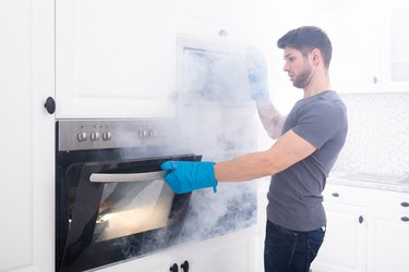 Man Opening Oven Filled With Smoke