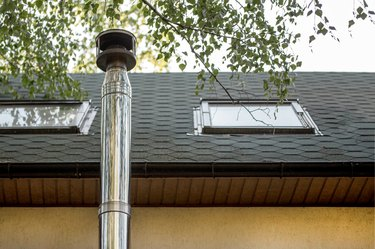 Stainless steel chimney flue on tile-covered roof with windows at country cottage