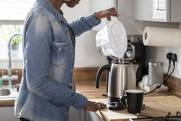 Woman pouring water into kettle in kitchen
