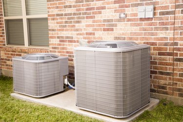 Two air conditioning units outside brick home.