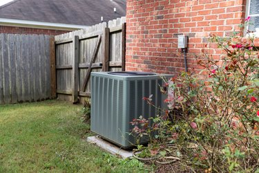 Air conditioner condenser unit sitting next to brick home with fence