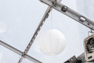 Closeup of hanging one white paper party ball or sphere light lantern from ceiling in restaurant building venue with fan, speakers