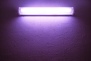 Germicidal ultraviolet lamp glows on a rough wall.