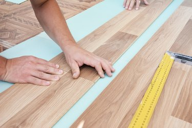 Wood laminate flooring installation: Laminate flooring installers are installing laminate hardwood planks over a soundproofing underlayment, insulation.