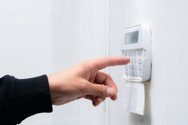 Hand entering alarm system password of an apartment, home or business office. Surveillance and protection console against rubbery and thief