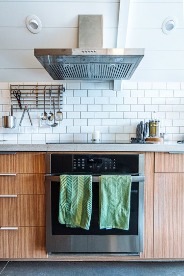 Wide Angle Shot of Green Hand Towels on the Front of a Oven and Range Stove in a Trendy Kitchen