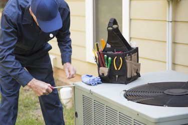 Technician services outside AC unit and generator.