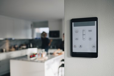 Thermostat app on digital tablet mounted over white wall at home