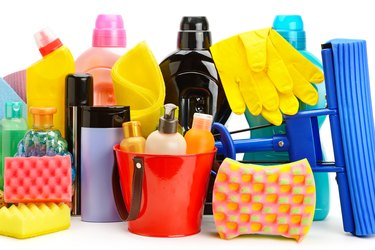 Collection of various household cleaning products isolated on a white background.