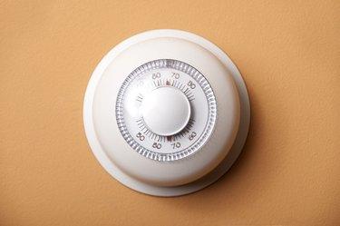 Round, white analog-dial thermostat on peach wall