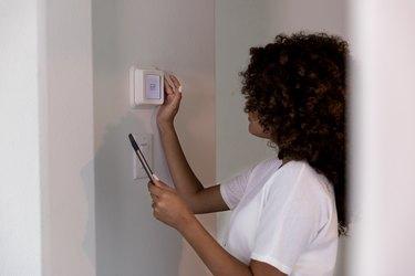 Female homeowner adjusts thermostat
