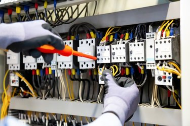 Electricians work to connect electric wires in the system, switchboard, electrical system in Control cabinet.
