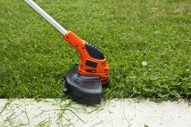 Weed Trimmer Trimming Grass Along Sidewalk