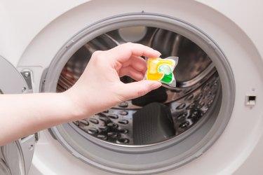 female hand puts laundry pod into the washing machine