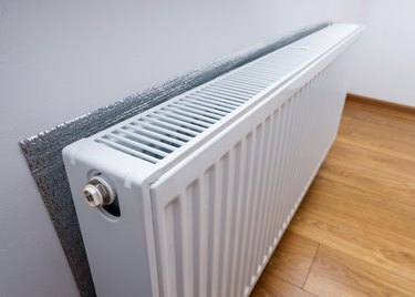 White metal heating radiator forming part of a central heating system with energy-efficient thermal insulation on the wall