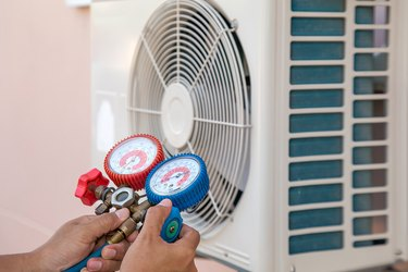 Mechanic air repair using manifold gauge for filling home air conditioner and checking maintenance outdoor air compressor unit.