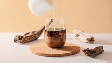Milk cream pours into a transparent glass of black coffee on a minimalistic beige natural wooden background.