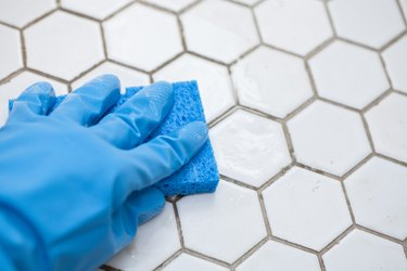 blue cleaning gloves holding a sponge cleaning a tile floor