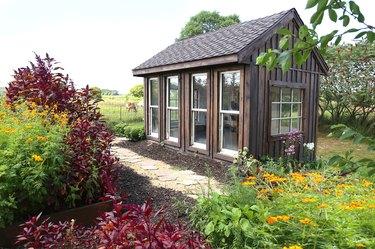 Old Wooden Garden Shed Near Horse Pasture in Lush Summer Cottage Garden