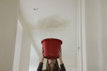woman holding out a bucket to stop a roof leak