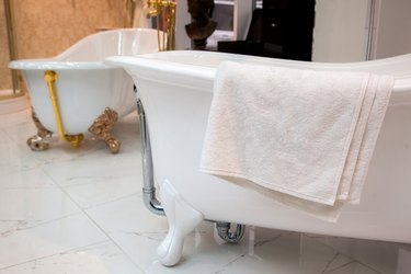 a white terry towel lies on a cast-iron bathtub on a ceramic tile floor in a store.