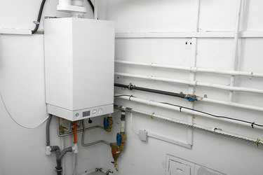 Corner of a room with white boiler and connectors
