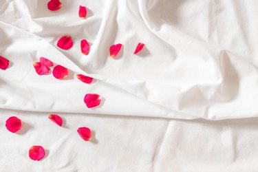 Top view of pink rose petals on white bed sheets on honeymoon. Surprise romantic concept background