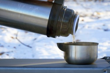 Pours a hot drink from a thermos into a steel mug in winter against the background of snow